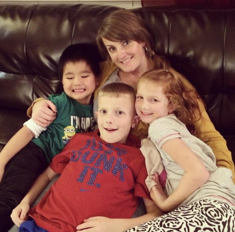 Three kids crammed on mom's lap.